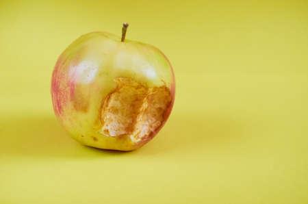 A bitten Apple lies on a colored background. Close up Stok Fotoğraf