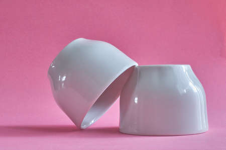 Two white ceramic cups without handles on a pink background