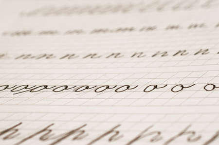 Page of a school notebook with handwritten letters of the English alphabet in close-up