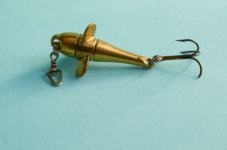Fishing equipment. One metal fishing lure on a blue background Close up