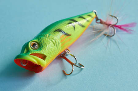 Fishing equipment. One plastic Wobbler close-up on a blue background
