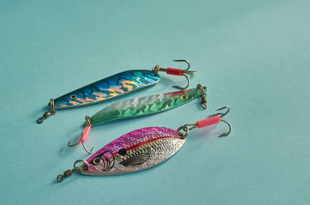 Fishing equipment. Three metal fishing lures close up on a blue background