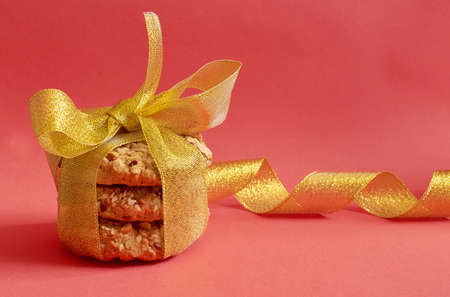 Round cookies with cereals and seeds, tied with a gold ribbon on a red background 스톡 콘텐츠
