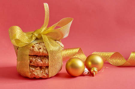 Round cookies with cereals and seeds tied with a gold ribbon, Christmas toys on a red background 스톡 콘텐츠