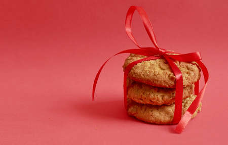 Cookies with cereals tied with a red ribbon lying on a red background 스톡 콘텐츠