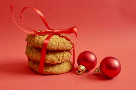 Round cookies with cereals and seeds tied with a red ribbon, Christmas toys on a red background