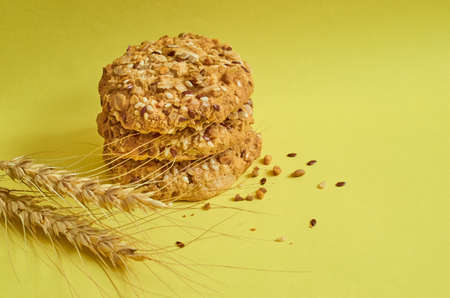 Three cookies with flakes and sesame seeds and a spikelet of wheat on  yellow