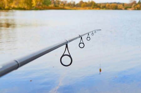 Rings on a fishing rod with a fishing line threaded through them and a lure close-up on the background of water Stok Fotoğraf