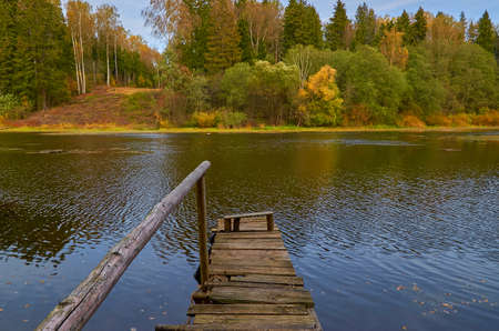 Autumn landscape. Old wooden bridge with handrail on the lake shore. Sunny autumn day