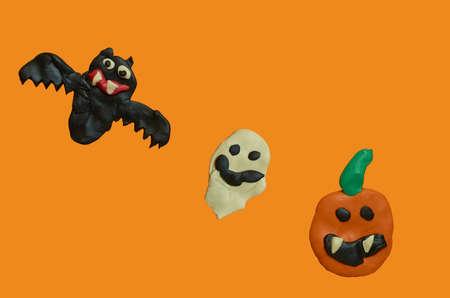 Children's crafts made of plasticine. Halloween. Bat, Ghost and pumpkin on an orange background.