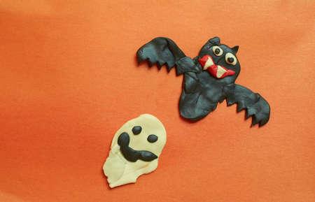 Children's crafts made of plasticine. Halloween. Bat and Ghost on an orange background Stok Fotoğraf