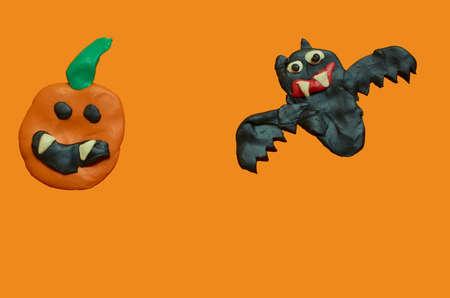 Children's crafts made of plasticine. Halloween. Bat and pumpkin on orange background