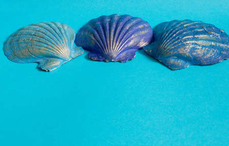 Marine layout. Three shells painted in blue, blue and purple on a blue background. Space for text Stok Fotoğraf