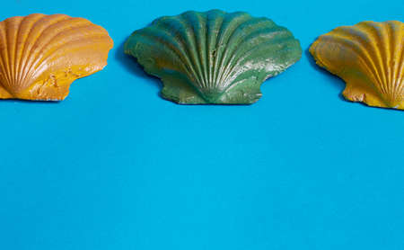 Three seashells painted orange, yellow, and green, and two small white seashells on blue Stok Fotoğraf