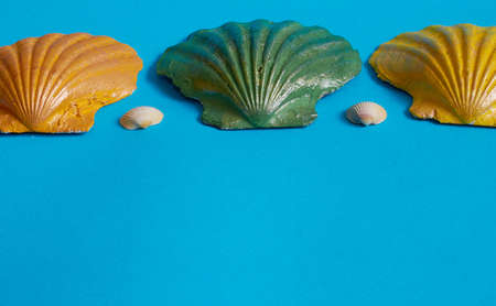 Marine layout. Three seashells painted orange, yellow, and green, and two small white seashells on a blue background. Space for text Stok Fotoğraf