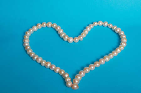 Heart-shaped pearl beads on a blue background. Space for text Stok Fotoğraf