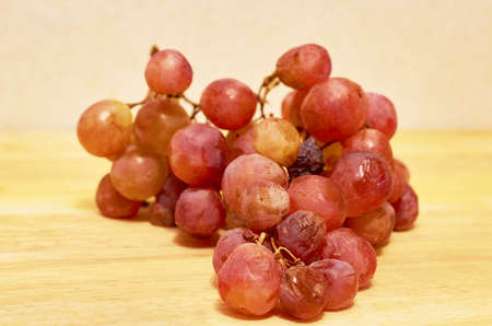 A spoiled bunch of grapes lies on a wooden surface. Close up. Macro
