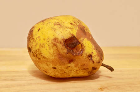 One rotten yellow pear is lying on the wooden surface. Close up Stok Fotoğraf
