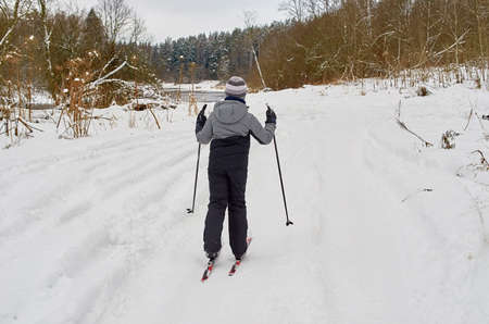 A boy skis on a winter road along the river. View from behind.