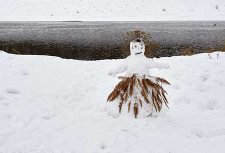 A sad snowman in a cane skirt stands on the river bank on a winter day.
