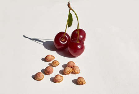 Red ripe cherry and lots of cherry pits on a gray textured background. Bright light, hard shadows. Horizontal format