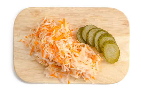 Sauerkraut with pickles on a wooden cutting board isolated. Top view.