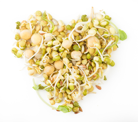Heart. Mix of sprouted flax, peas, mung bean, sunflower, wheat, lentil seeds isolated on white background. vegan, raw food diet