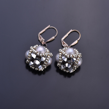 Grey pearl earrings with silver beading on a dark background. Beadwork Imagens