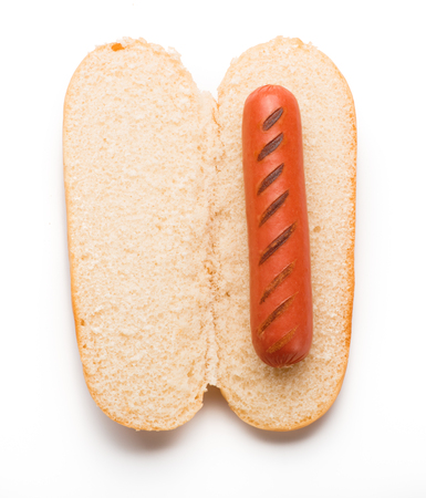 Hot dog bun with grilled sausage isolated on white background. Top view.