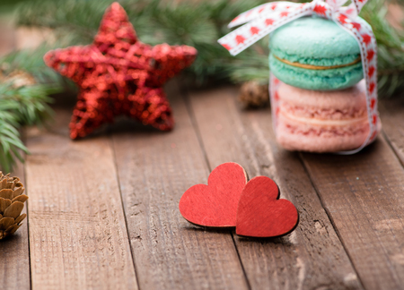Two red wooden hearts with star on the table. Macaroons. Christmas decoration. Copy space. Valentine. Love.