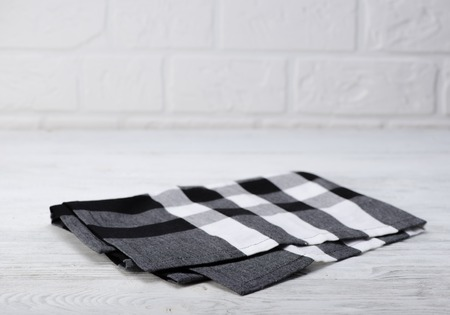 Black And White Napkin. The Checkered Tablecloth On Wooden Table. Brick  Wall Background.