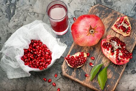 Pomegranate fruits with grains and leaves on the table. Make juice. Top view.