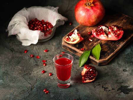 Glass of pomegranate juice. fruits with grains and leaves on the table. Make . Dark moody. Stock Photo