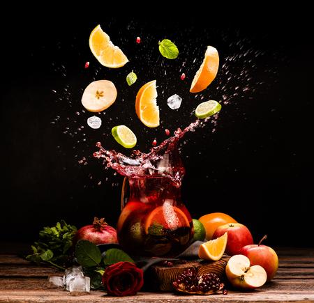 Sangría. frutas volar. Manzana, naranja, limón, la granada, la menta. Beber. Vino. Concepto. Moody oscuro. España. jarra de bebida. tarro de jugo.