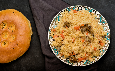 Pilaf on plate with oriental ornament and Traditional Asian breads - churek. Central-Asian cuisine - plov. Top view.