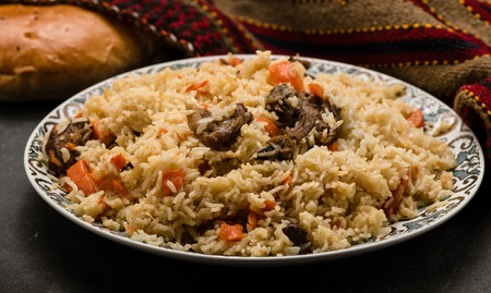uzbek: Pilaf on plate with oriental ornament and Traditional Asian breads - churek. Plov.