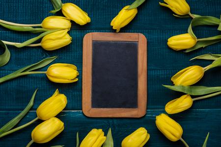 Yellow tulips on dark blue background with antique halk wooden board.