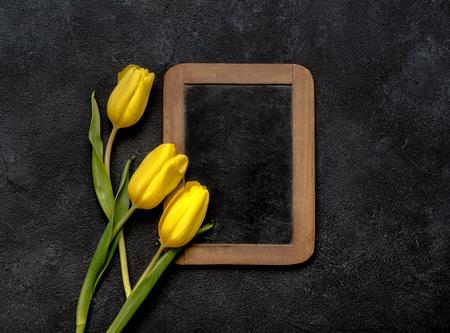 Yellow tulips on dark background with antique halk wooden board.