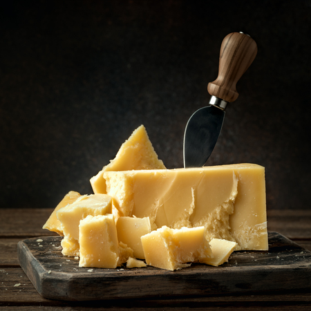 Parmesan cheese on a wooden board with knife. Pieces of parmigiano reggiano cheese.