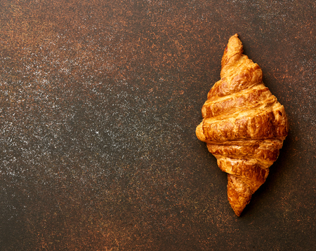 breadbasket: Croissant on brown concrete background. Bakery product on brown concrete background. Copy space. Stock Photo
