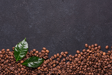 Coffe beans with coffe leaves on black background