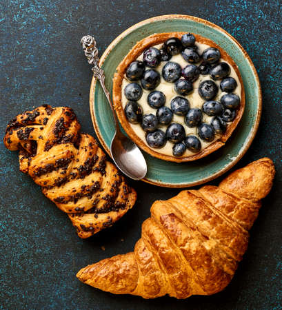 breadbasket: Breakfast with croissant, tart. Bakery products with copy space.