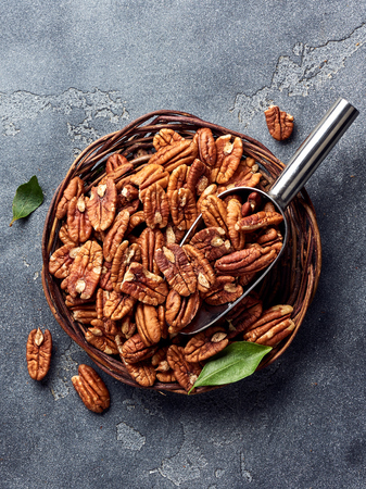 Pecan nuts and scoop on gray table Standard-Bild