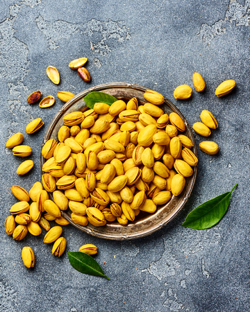 Yellow pistachios spiced with turmeric on gray background. Top view of nuts. Banque d'images