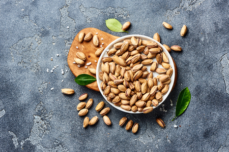 Salted Pistachios nuts with green leaves and scoop. Top view of snacks.