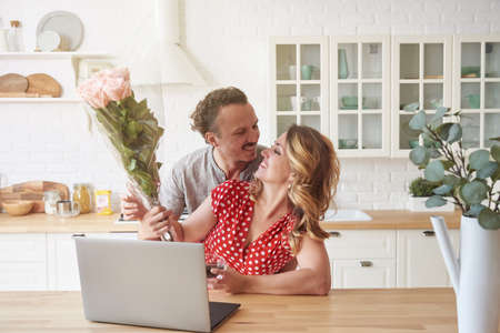 Happy family couple in modern kitchen with laptop and coffee. A man in love gives flowers to a woman.