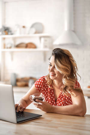 Happy beautiful woman drinking coffee. Woman working on a laptop in kitchen.