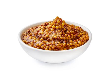 Whole grain mustard. French mustard in white bowl isolated. Foto de archivo - 112465919