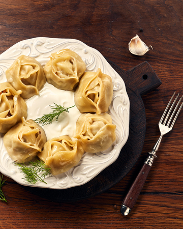 Asian steamed dumplings Manti with dill and garlic on wooden background. Banque d'images