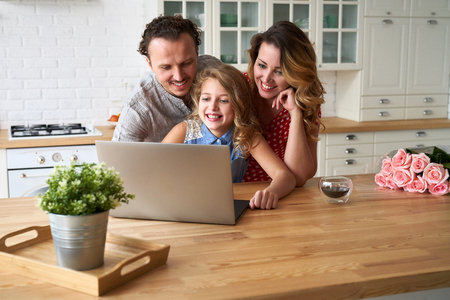 Young happy family surfing internet with laptop on table at kitchen